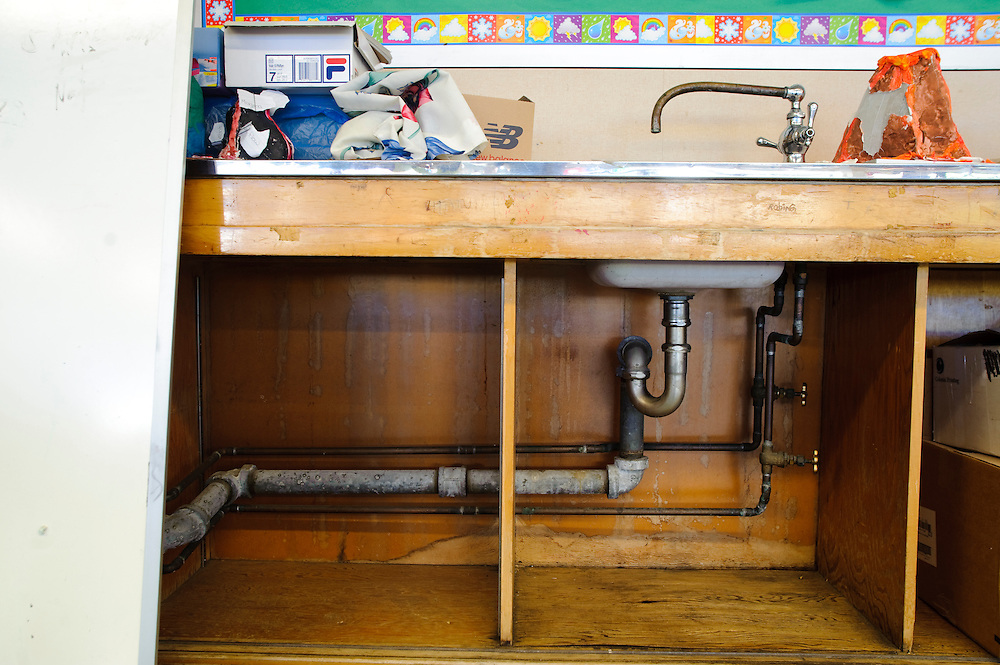(photo by Matt Roth).Friday, May 14, 2010..There is no water flowing through the pipes in the Ms. Arsenia Butal's classroom. Too much lead makes the water dangerous for consumption. The piping cover is also missing. The Eighth grade science teacher also reports that students will sometimes hide underneath the sink and play with the faucets below. ..The building housing the Baltimore Freedom Academy, a grade 6-12 Baltimore public charter school focusing in social justice, was built in 1960. Fifty years later, the school is in disrepair. Old pipes make water from the fountains undrinkable. Asbestos makes repairing/replacing the pipes a hazard. The school has no air conditioning which makes the year-round school unbearable in the summer. The most derelict area is the boys locker room, where students are not allowed.