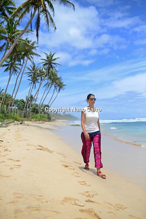Young woman walking on the beach between Weligama and Ahangama, Sri Lanka