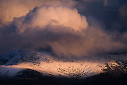 Sunset washed billowing clouds race across the snowy faces of the majestic Snowdonia mountain range in North Wales, belying the bitter cold conditions on the summits under the warm light