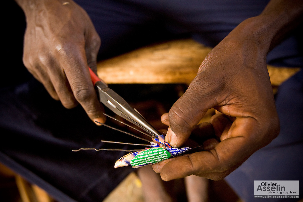 A man makes insects from recycled metal cans at the Village Artisanal de Ouagadougou, a cooperative that employs dozens of artisans who work in different mediums, in Ouagadougou, Burkina Faso, on Monday November 3, 2008.