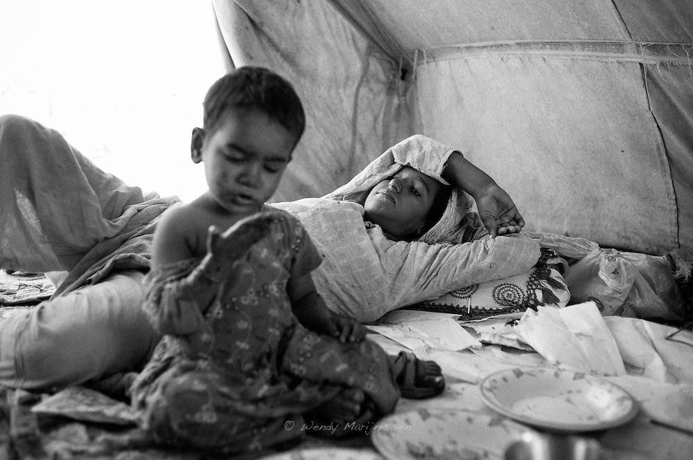 Hamida takes a little rest after food. Living in the camp is especially hard on pregnant women as they struggle with the warmth of the tents. Karachi, Pakistan, 2010
