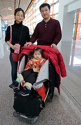Chinese family with a single young daughter travelling through the new Terminal 3 at Beijing Airport during Chinese New Year 2009
