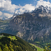 """The village of Gimmelwald nestles in Lauterbrunnen Valley under Jungfrau and peaks of the Lauterbrunnen Wall, in the Berner Oberland, Switzerland, the Alps, Europe. The mountain peaks of Jungfrau, Mönch, Eiger, and Wetterhorn rise right to left. UNESCO lists """"Swiss Alps Jungfrau-Aletsch"""" as a World Heritage Area (2001, 2007). Published on cover of the Ryder-Walker Alpine Adventures """"Inn to Inn Alpine Hiking Adventures"""" Catalog 2007."""