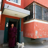 TONGREN, APRIL 4, 2012 : a Tibetan stands at the entrance of  a settlement for nomads created by the local government.