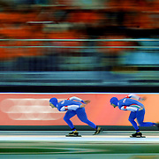 The Italian team of Enrico Fabris (far left, #3), Ippolito Sanfratello (middle, #5) and Matteo Anesi (far right, #1) speed around the track on their way to a gold medal in the Men's Team Pursuit Speed Skating Finals at the Oval Lingotto in Turin, Italy on Thursday February 16, 2006. The Italian team beat out the Canadian team with a new Olympic record time of 3:43.64. The U.S. men finished 6th in the event and the U.S. women finished 5th..(Photo by Marc Piscotty / © 2006)