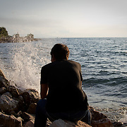 An Afghan migrant sits on the beach near the Greek city of Patras as ships sail to Italy in the distance.