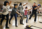 "Assistant coach Tom Richardson works with Xiao Yai, 18, left, Aliya Kamaletdinova, 17, Gabby Garcia, 15, and Xochitl Garcia, 16, during practice. ""We're trying to coach the girls to understand the principles and basics of bowling and adapt that to their own personal style,"" says head coach Oscar Garnica. ""And the basics is just literally how to hold a bowling ball,"" says Richardson. ""A lot of these girls literally don't know how to hold a bowling ball...we've literally taken girls from this season that were gutter to gutter -- they threw more gutters than they knocked down pins -- and worked them up to varsity this year."""