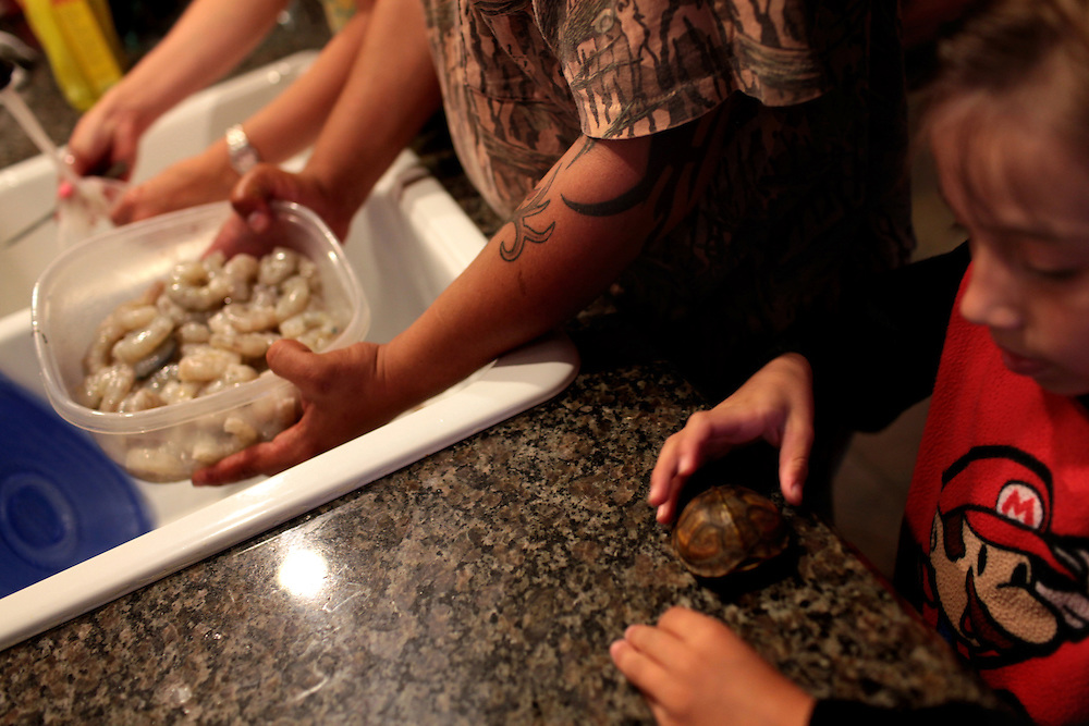 Jami Serigne, left, and her husband Kimmie Serigne, center, clean shrimp while their son Morgan Serigne, 6, plays with his pet turtle as they prepare to have fried shrimp for dinner in their home on the outskirts of Chalmette, LA on May 21st, 2010. The shrimp was caught in the local bayou to be used for bait after the shrimping industry was shut down after the BP oil spill in the Gulf of Mexico.