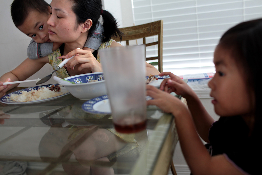 Exhausted, Van Huynh spends time with her children Quentin Vo, 2, left, and Renee Vo, 5, right, at their home in Marrero, LA on May 23, 2010. Van Huynh found a job in a nail salon working long hours to earn money for the family after her husband Minh Vo lost his income after shrimp season was closed because of the BP oil spill in the Gulf of Mexico. By the time the $5,000 check from BP arrived, it was spent within days paying bills. Forced from his shrimp boat, Minh Vo began cooking, cleaning and looking after the children at home.