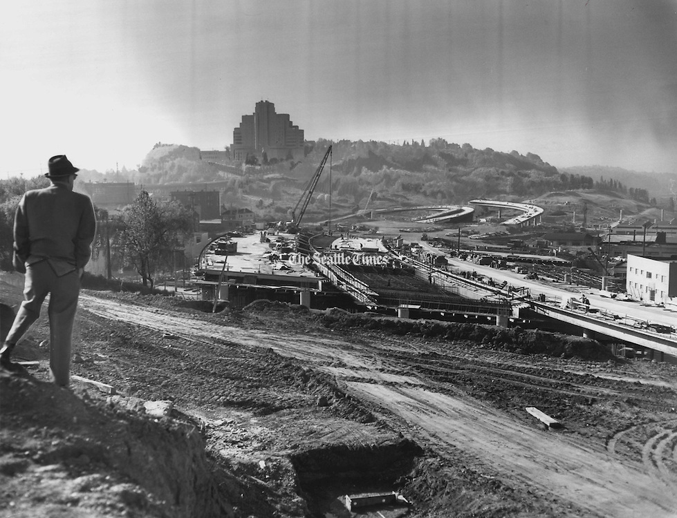 Workmen with machines stay busy as work progresses on construction of the Connecticut Street Interchange of the freeway on May 16, 1965. Connecticut Street was renamed Royal Brougham Way after the beloved Seattle sports writer. In the background is the PacMed building, also known as Pacific Tower. (Johnny Closs / The Seattle Times)