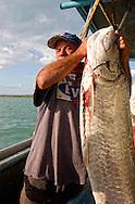 Fisherman with tarpon off the coast of Ciego de Avila in the Cayos de Ana Maria, Cuba.