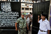 An Egyptian soldier and police officer stand guard at the entrance of of a polling station during the historic democratic Presidential election May 23, 2012 in Cairo Egypt. Coming 15 months after the revolution that toppled the regime of former President Hosni Mubarak, the election will not only decide the leader of the country, but also set the tone and decide the course by which the country moves forward in democracy and reform.  (Photo by Scott Nelson)