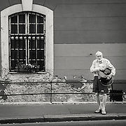 Elderly man with two bags in his hands standing on a sidewalk in Budapest Hungary
