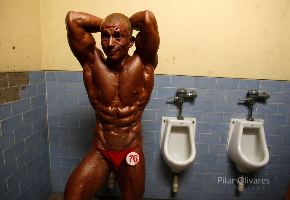 A competitor flexes his muscles inside a bathroom before a bodybuilding competition in Lima January 30, 2010.