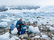 """Tom and Carol Dempsey visit the continent of Antarctica at Neko Harbor, Graham Land, Antarctic Peninsula. We cruised here on the red and white ship M/S Explorer in February 2005 and made a wet landing using Zodiac boats. Glaciers calve icebergs into the Southern Ocean. An adult Gentoo Penguin (Pygoscelis papua) has a bright orange-red bill and a wide white stripe extending across the top of its head. Chicks have grey backs with white fronts. Of all penguins, Gentoos have the most prominent tail, which sweeps from side to side as they waddle on land, hence the scientific name Pygoscelis, """"rump-tailed."""" As the the third largest species of penguin, adult Gentoos reach 51 to 90 cm (20-36 in) high. They are the fastest underwater swimming penguin, reaching speeds of 36 km per hour. Published in November/December 2008 Sierra Magazine, Sierra Club Outings. For licensing options, please inquire."""