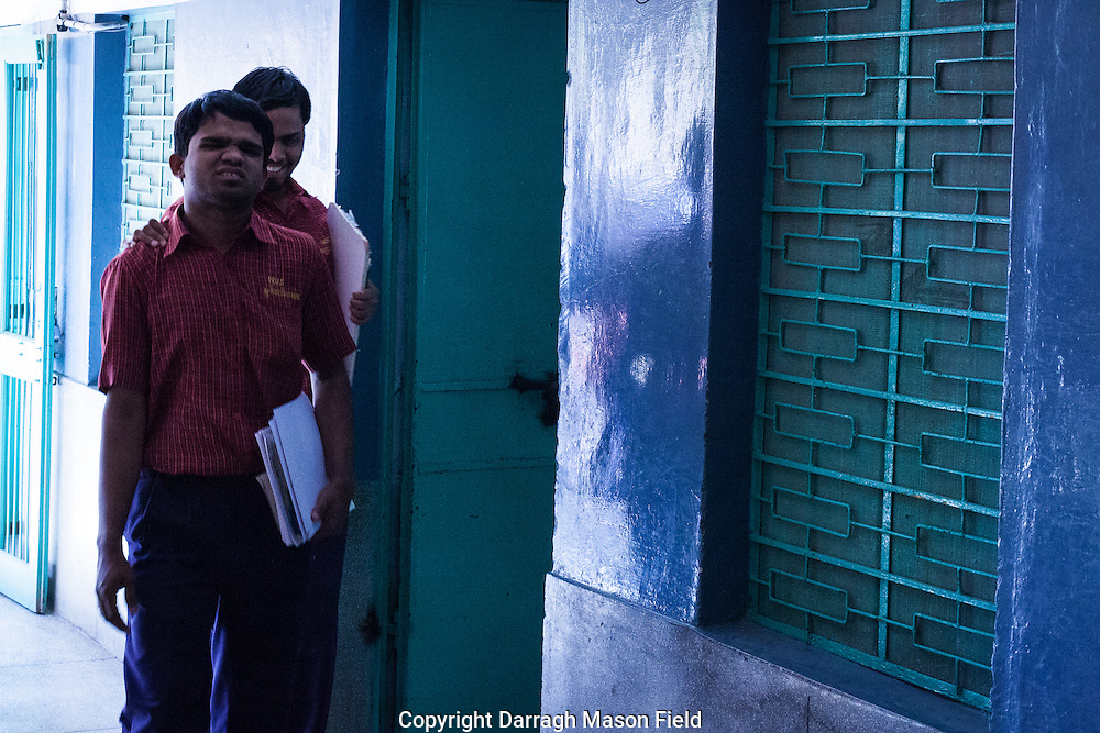 Blind and visually impaired students guide each other around the school.