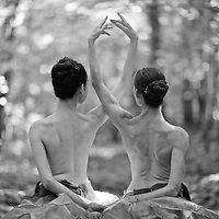 Two ballerinas dance in a forest.