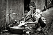 Washing dishes in Klong Toey, Bangkok, Thailand. PHOTO BY LEE CRAKER