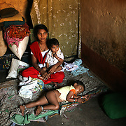 """Kavita Kurbati, 18, sits inside her family home in the bustling town of Gokak, India, waiting for a customer. In her arms is daughter Chaitra (1) and sleeping peacefully at her feet is Rakshita (3). When Kavita reached puberty, her mother, drawing on an ancient religious tradition, dedicated her to the Hindu deity, Yellamma, thus turning her daughter into a Devadasi or """"female servant of god"""". This meant that Kavita was """"married"""" to Yellamma, which made her ineligible to marry a mortal. Instead, as a means of pleasing Yellamma and bringing better fortunes to her family, she would serve as a """"temple prostitute"""", satisfying the needs of men in her community."""