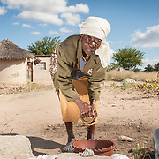 CAPTION: Johana washes dishes outside her home. The Bindagombe Irrigation Scheme will provide more borehole pumps and thus access to water for cleaning, sanitation and cooking. LOCATION: Mawoneke Village, Chivi District, Masvingo Province, Zimbabwe. INDIVIDUAL(S) PHOTOGRAPHED: Johana Nyuke.