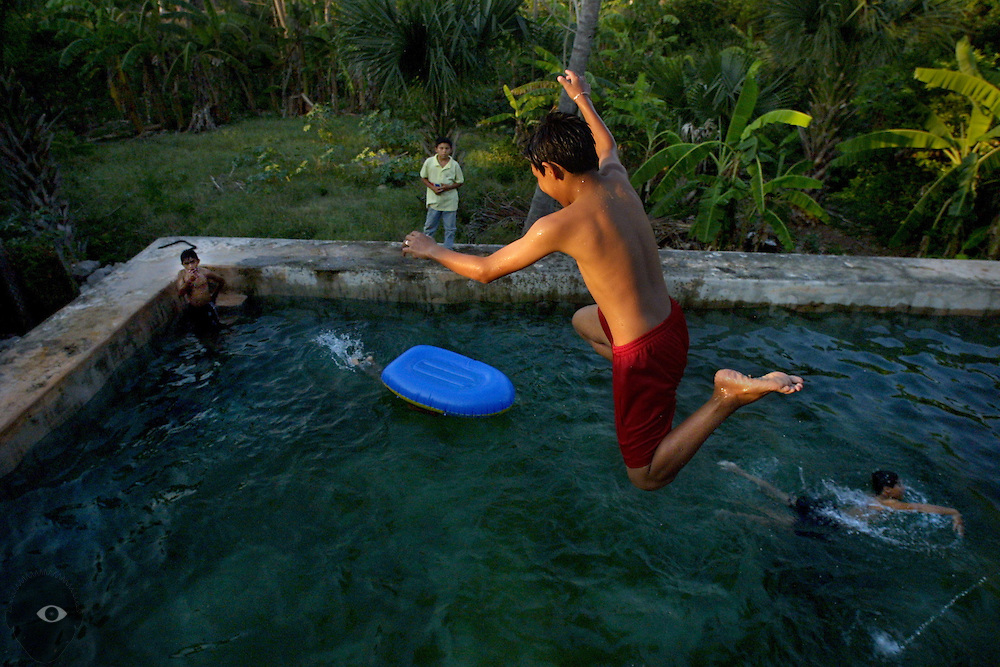 Boys dive and swim in the rock-lined pool at the centuries-old San Miguel Arcangel Church in Mani, Yucatan.