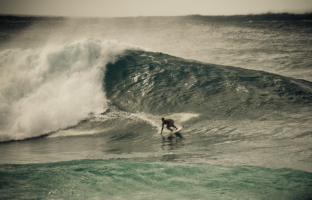 A surfer rides a wave at Banzai Pipeline, Oahu, Hawaii, USA.