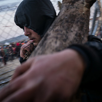A young man is seen carring wood used for cooking and heating in the make shif camp next to the Greek Macedonian border not far from the Greek village of Idomeni, Greece. FEDERICO SCOPPA/CAPTA