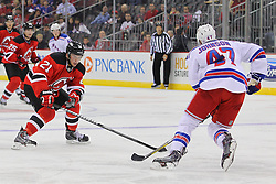 Sep 16, 2013; Newark, NJ, USA; New Jersey Devils center Andrei Loktionov (21) defends against New York Rangers defenseman Aaron Johnson (47) during the second period at Prudential Center.