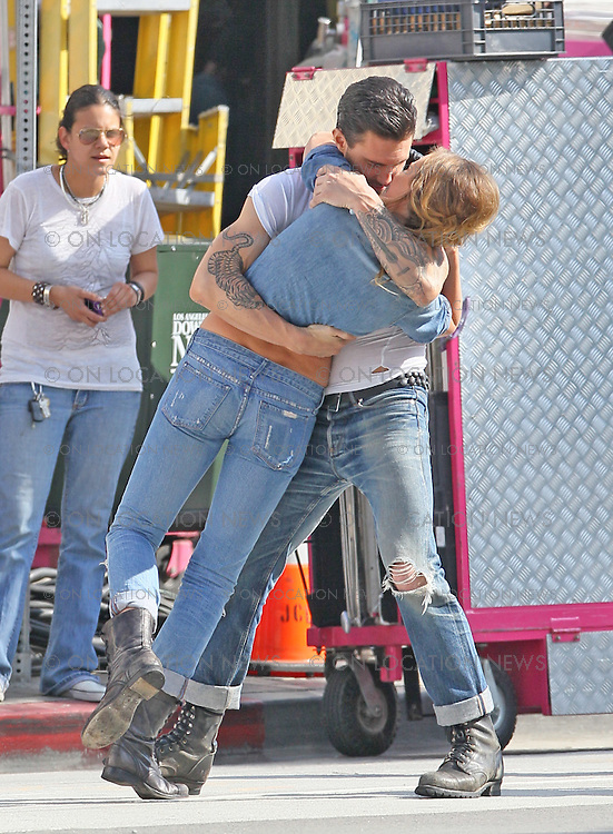 "May 15th 2010. Los Angeles, CA. ***EXCLUSIVE*** Adam Levine with his beautiful Russian Supermodel girlfriend Anne Vyalitsyna  filming a Maroon 5 Music Video for their song; ""Misery"". The sexy couple filmed various scenes of loving affection with passionate kissing followed by scenes of humorous violence and destruction. In this action packed Music Video, Adam Levine and his band mates are fleeing from Anne Vyalitsyna who is humorously trying to kill them in various ways. Scenes include a missile gun attack and knife throwing from Anne, Adam being hit by a car while running away, Adam being close lined by Anne off a motorcycle that he is fleeing on,  Adam being kicked through a cafe window as well as being ejected from the window of a high rise building. The couple were constantly kissing, hugging and holding hands while on set. They both shared a big luxury trailer while not filming. Photo by Eric Ford/ On Location News. 818-613-3955. info@onlocationnews.com"