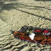 A Cuban boy sleeps under a palm tree at Guanabo Beach in Cuba.