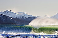 Cold winter surf breaks against an offshore breeze in Homer, Alaska. The snowy Kenai mountain range rises from Kachemak Bay in the background.