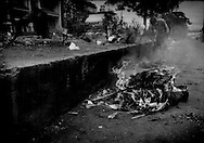 Man burnes wood, plastic, anything that burns of Radial Road 10 which runs along the harbor in the Tondo District of Manila where squatters have built vast slums over the decades since the end of the Second World War.  Now several generations of families have occupied makeshift homes in Tondo, left to live by their wits.<br /> <br /> While the extreme poverty rate in the region dropped significantly between 2005 and 2008, the Philippines' poverty rate remained largely unchanged.  In fact, poverty has intensified on the poor.  According to the National Statistics Coordination Board (NSCB) in 2006, 28.8% of families lived on less than US$1.25/ day.  By 2012, 27.9 % of Filipinos were living below the poverty line.  <br /> <br /> What what changed was the income per family needed to escape extreme poverty.  While in 2006, a family would need to earn US$39.09 / month to escape extreme poverty, that figure rose in the most recent NSCB survey to US$ 181.89/month, clear showing how inflation is weighing heaviest upon that society's poor.