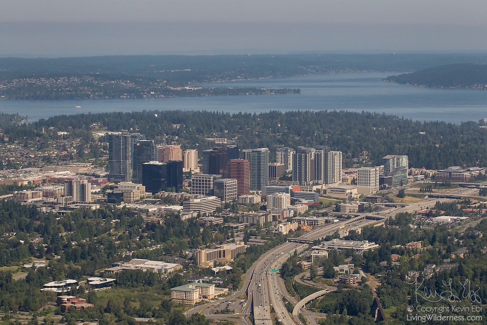 The core of downtown Bellevue, Washington is visible in this aerial view. Among the buildings visible, from left to right, are Bellevue Square, Lincoln Square, Bellevue Place, Bravern, Bellevue City Hall and the Meydenbauer Center. Interstate 405 runs in the foreground; Lake Washington is visible in the background.
