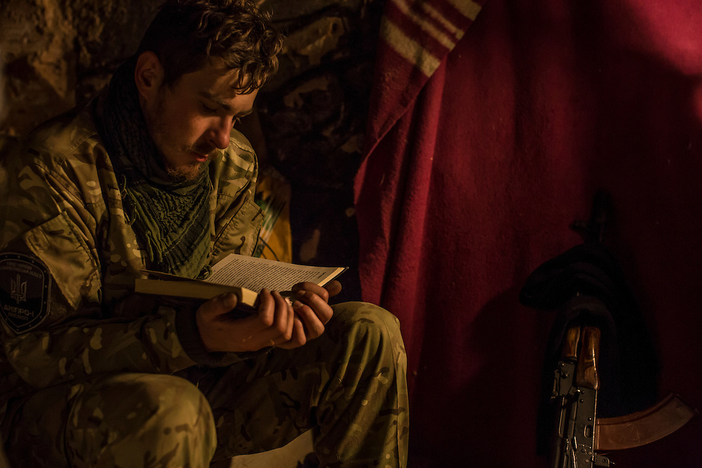 "PERVOMAISKE, UKRAINE - NOVEMBER 17, 2014: ""Patrick,"" a member of the 5th platoon of the Dnipro-1 brigade, a pro-Ukraine militia, who chose not to give his name because he is from a nearby town and fears for the safety of his family, reads a book inside a bunker where he sleeps at their post underneath a bridge in Pervomaiske, Ukraine. CREDIT: Brendan Hoffman for The New York Times"