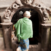 An elderly woman visits a shrine in Nepal's Bhaktapur Village.