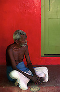 Man against red wall. Small shrine within precinct of Kataragama Devale.