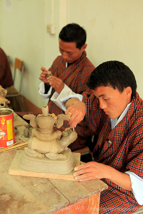 Asia, Bhutan, Thimpu. Sculpting students at the National Institute for Zorig Chusum, or traditional arts and crafts.