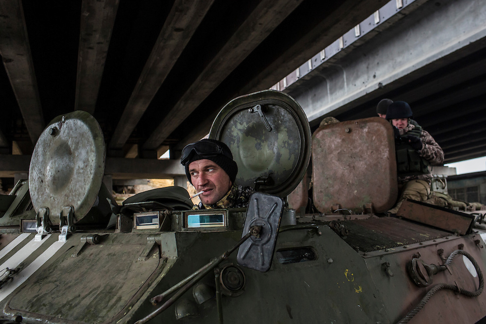 PERVOMAISKE, UKRAINE - NOVEMBER 19, 2014: The driver of a tracked armored personnel carrier inside his vehicle at a  base under a bridge in Pervomaiske, Ukraine. CREDIT: Brendan Hoffman for The New York Times
