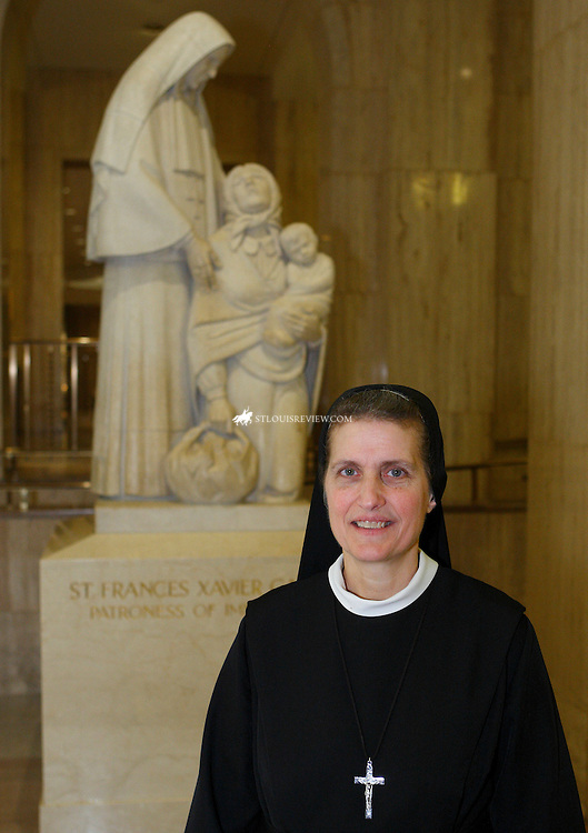 Sister Eva-Maria Ackerman poses near a statue of St. Frances Xavier Cabrini after speaking at a press conference at the Basilica of the National Shrine of the Immaculate Conception in Washington Jan. 30. Sister Eva-Maria announced that the Vatican has initiated an apostolic visitation to find out why the numbers of women religious have decreased during the past 40 years. Sister Eva-Maria, a member of the American Province of the Sisters of St. Francis of the Martyr St. George, said she believes it's the first study of its kind in the U.S. (CNS photo/Paul Haring) (Jan. 30, 2009) See APOSTOLIC-VISITATION Jan. 30, 2009.