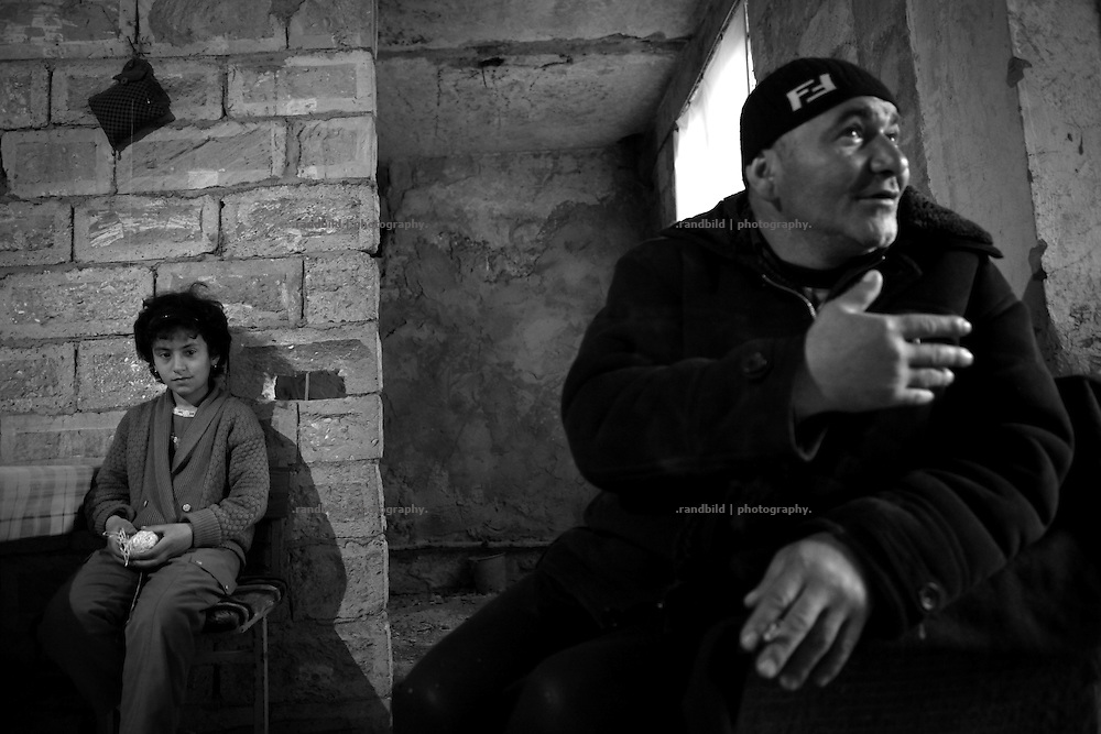 "Father Micha gestures while his daughter sit on a chair in their flat under construction. This image is part of the photoproject ""The Twentieth Spring"", a portrait of caucasian town Shushi 20 years after its so called ""Liberation"" by armenian fighters. In its more than two centuries old history Shushi was ruled by different powers like armeniens, persians, russian or aseris. In 1991 a fierce battle for Karabakhs independence from Azerbaijan began. During the breakdown of Sowjet Union armenians didn´t want to stay within the Republic of Azerbaijan anymore. 1992 armenians manage to takeover ""ancient armenian Shushi"" and pushed out remained aseris forces which had operate a rocket base there. Since then Shushi became an ""armenian town"" again. Today, 20 yeras after statement of Karabakhs independence Shushi tries to find it´s opportunities for it´s future. The less populated town is still affected by devastation and ruins by it´s violent history. Life is mostly a daily struggle for the inhabitants to get expenses covered, caused by a lack of jobs and almost no perspective for a sustainable economic development. Shushi depends on donations by diaspora armenians. On the other hand those donations have made it possible to rebuild a cultural centre, recover new asphalt roads and other infrastructure. 20 years after Shushis fall into armenian hands Babies get born and people won´t never be under aseris rule again. The bloody early 1990´s civil war has moved into the trenches of the frontline 20 kilometer away from Shushi where it stuck since 1994. The karabakh conflict is still not solved and could turn to an open war every day. Nonetheless life goes on on the south caucasian rocky tip above mountainious region of Karabakh where Shushi enthrones ever since centuries."