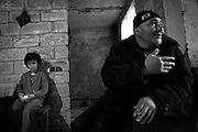 """Father Micha gestures while his daughter sit on a chair in their flat under construction. This image is part of the photoproject """"The Twentieth Spring"""", a portrait of caucasian town Shushi 20 years after its so called """"Liberation"""" by armenian fighters. In its more than two centuries old history Shushi was ruled by different powers like armeniens, persians, russian or aseris. In 1991 a fierce battle for Karabakhs independence from Azerbaijan began. During the breakdown of Sowjet Union armenians didn´t want to stay within the Republic of Azerbaijan anymore. 1992 armenians manage to takeover """"ancient armenian Shushi"""" and pushed out remained aseris forces which had operate a rocket base there. Since then Shushi became an """"armenian town"""" again. Today, 20 yeras after statement of Karabakhs independence Shushi tries to find it´s opportunities for it´s future. The less populated town is still affected by devastation and ruins by it´s violent history. Life is mostly a daily struggle for the inhabitants to get expenses covered, caused by a lack of jobs and almost no perspective for a sustainable economic development. Shushi depends on donations by diaspora armenians. On the other hand those donations have made it possible to rebuild a cultural centre, recover new asphalt roads and other infrastructure. 20 years after Shushis fall into armenian hands Babies get born and people won´t never be under aseris rule again. The bloody early 1990´s civil war has moved into the trenches of the frontline 20 kilometer away from Shushi where it stuck since 1994. The karabakh conflict is still not solved and could turn to an open war every day. Nonetheless life goes on on the south caucasian rocky tip above mountainious region of Karabakh where Shushi enthrones ever since centuries."""