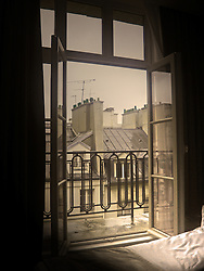 Open bedroom window in small Paris, France intimate hotel room.