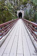 A Bridge over the Coquihalla River in Coquihalla Canyon Provincial Park near Hope, British Columbia, Canada.  These paths and tunnels were part of the Kettle Valley Railway which ran from Hope to Midway in British Columbia. The tunnels and railway were constructed in 1914 and are also known as the Quintette tunnels.