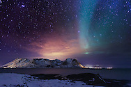 The winter sky is filled with the Aurora Borealis and the glow of Mortsund, a village in Norway's archipelago of Lofoten.