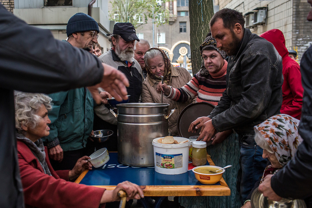 Hot soup is served to people in need of a free meal on Thursday, October 16, 2014 in Donetsk, Ukraine. Many older residents have not received pension payments in months and no longer have enough money to buy food. Photo by Brendan Hoffman, Freelance