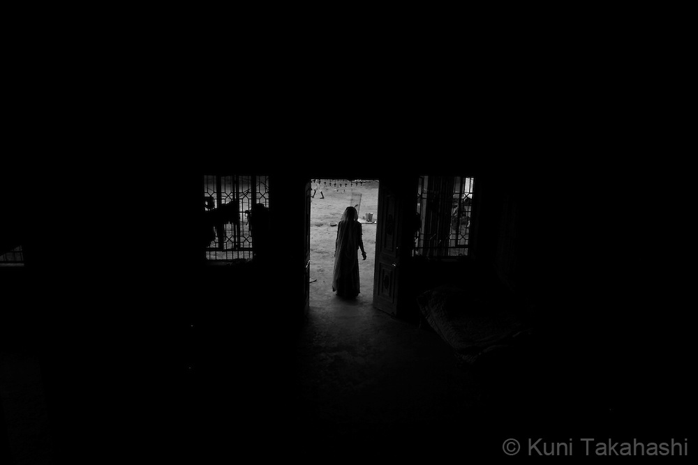 A woman stands at the entrance of her house in Ingonia in Rajasthan, India on Nov 16, 2009.