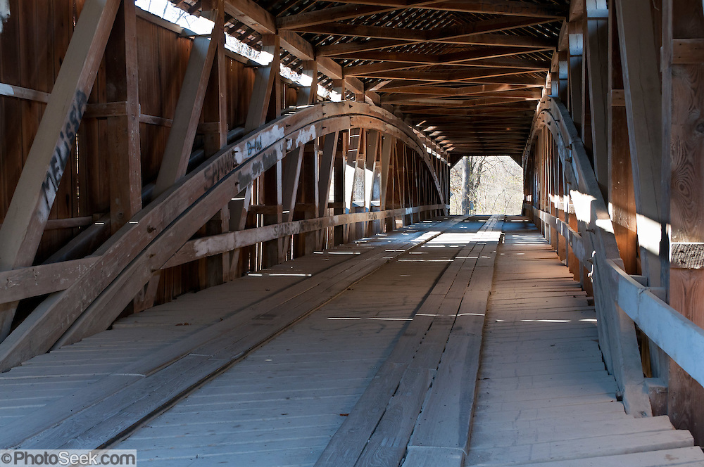 A Burr Arch Truss supports Cox Ford Covered Bridge, which was built in 1913 by J.A. Britton over Sugar Creek. Visit Turkey Run State Park in historic Parke County, Indiana, USA. Marked tourist routes visit many local covered bridges in rural farm country.