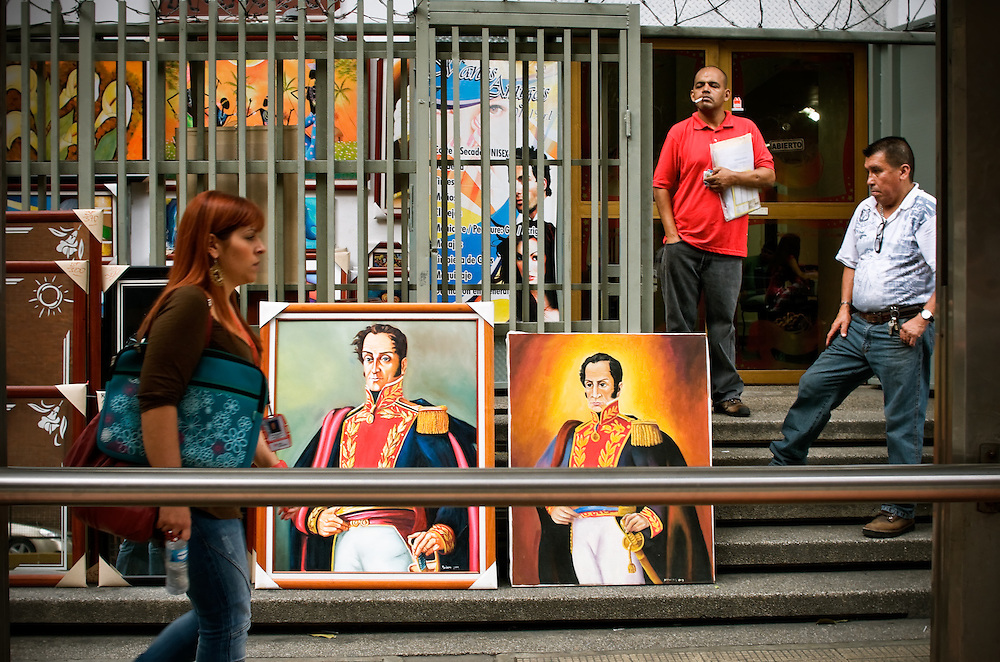 """An art vendor sells painted portraits of Venezuelan hero, Simón Bolívar in Caracas, Venezuela. Bolívar led the 19th Century revolutionary war against the Spanish Empire that won independence for Venezuela and several other Latin American countries. He died in 1830, however his image, name and legacy remain prominent throughout the country, politicized as a symbol of Chávez's politics and """"Bolivarian"""" Revolution. Manager of the art shop, Jose Antonio Arroyo, 53, said that he sells more paintings of Bolívar than any other piece of art, noting that most are purchased to adorn close-by government buildings and offices."""