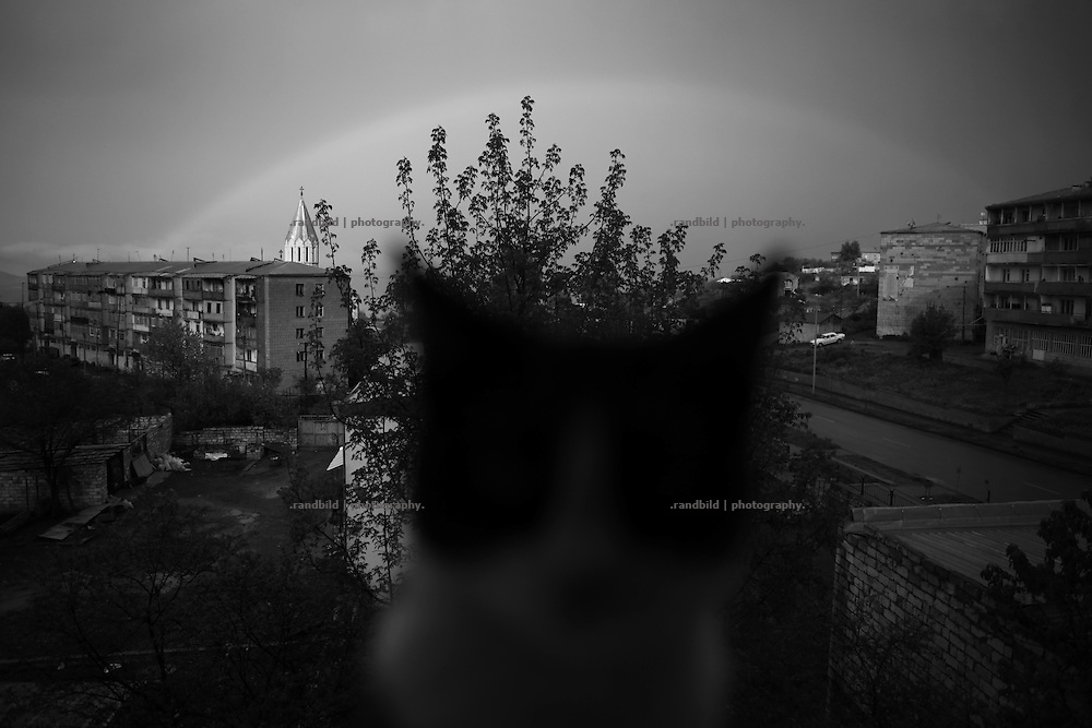 """A cat on window board while rain makes a rainbow visible above Shushi. This image is part of the photoproject """"The Twentieth Spring"""", a portrait of caucasian town Shushi 20 years after its so called """"Liberation"""" by armenian fighters. In its more than two centuries old history Shushi was ruled by different powers like armeniens, persians, russian or aseris. In 1991 a fierce battle for Karabakhs independence from Azerbaijan began. During the breakdown of Sowjet Union armenians didn´t want to stay within the Republic of Azerbaijan anymore. 1992 armenians manage to takeover """"ancient armenian Shushi"""" and pushed out remained aseris forces which had operate a rocket base there. Since then Shushi became an """"armenian town"""" again. Today, 20 yeras after statement of Karabakhs independence Shushi tries to find it´s opportunities for it´s future. The less populated town is still affected by devastation and ruins by it´s violent history. Life is mostly a daily struggle for the inhabitants to get expenses covered, caused by a lack of jobs and almost no perspective for a sustainable economic development. Shushi depends on donations by diaspora armenians. On the other hand those donations have made it possible to rebuild a cultural centre, recover new asphalt roads and other infrastructure. 20 years after Shushis fall into armenian hands Babies get born and people won´t never be under aseris rule again. The bloody early 1990´s civil war has moved into the trenches of the frontline 20 kilometer away from Shushi where it stuck since 1994. The karabakh conflict is still not solved and could turn to an open war every day. Nonetheless life goes on on the south caucasian rocky tip above mountainious region of Karabakh where Shushi enthrones ever since centuries."""