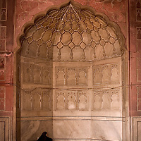 A woman sits and prays in one of the main alcoves in the front of the Jamma Masjid, Old Delhi. This is actually rare to see women here, as there is a womans section in the side of the mosque.
